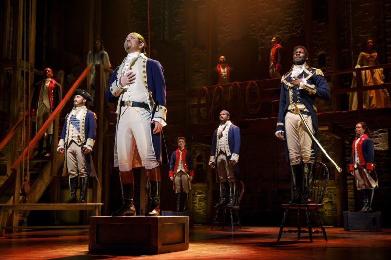 Alexander Hamilton, Marquis de Lafayette, Hercules Mulligan, and General George Washington watch the British Army surrender.