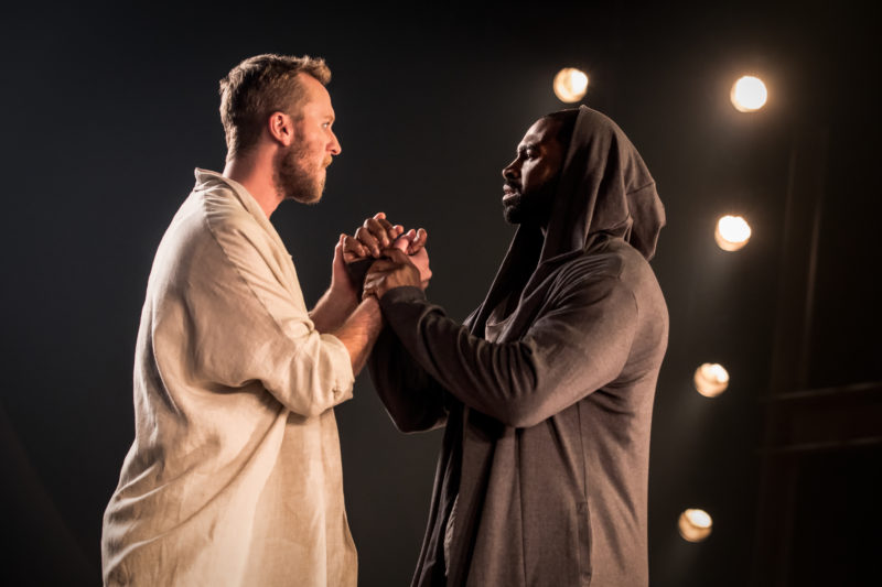 Jesus Christ and Judas hold hands looking at each other