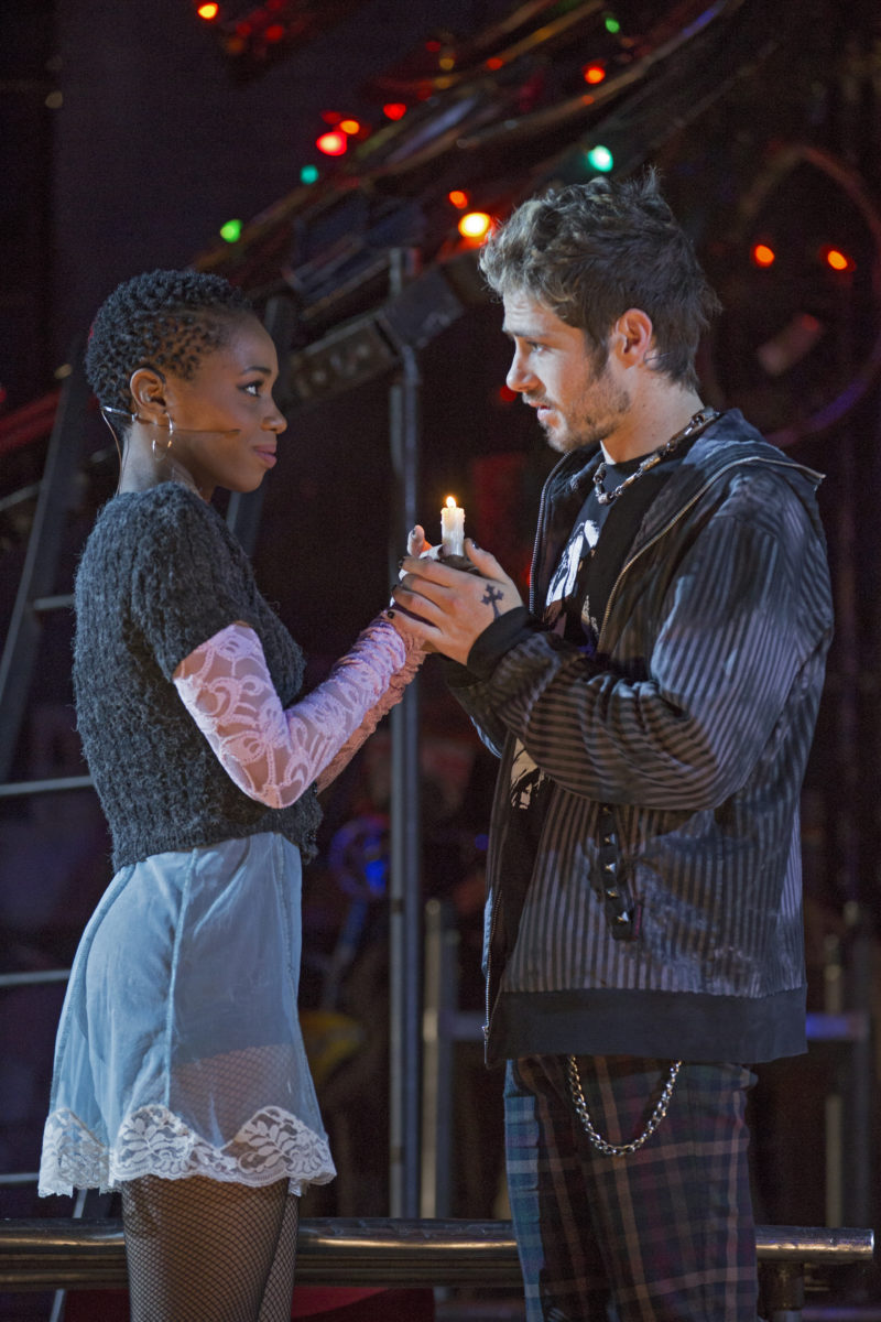 Young woman (Mimi) and young man in leather jacket (Rodger) hold a candle while staring into each other's eyes